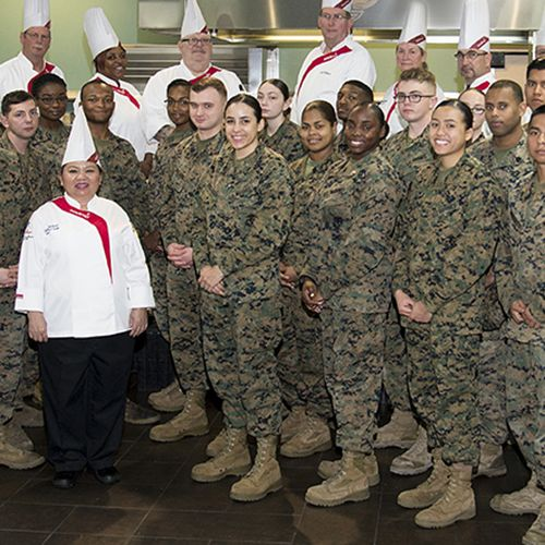 A group of chefs and military personnel standing together